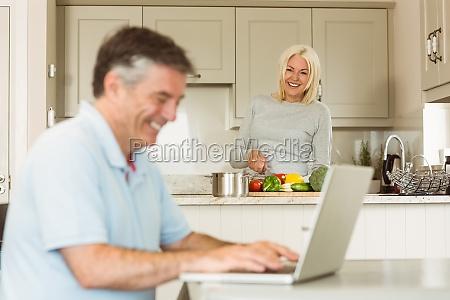 happy mature man using laptop while