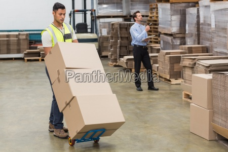 warehouse worker moving boxes on trolley