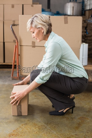 warehouse manager picking up cardboard box