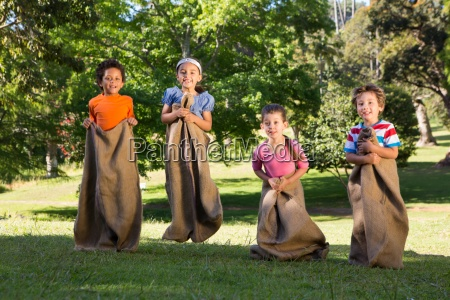 children having a sack race in