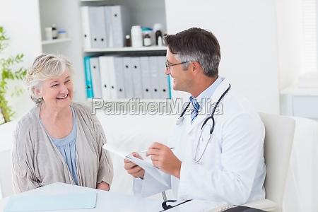 doctor writing prescriptions for senior female