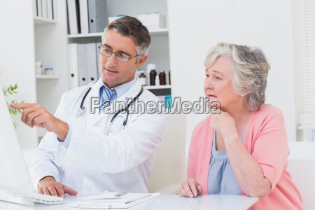 doctor showing reports to senior patient