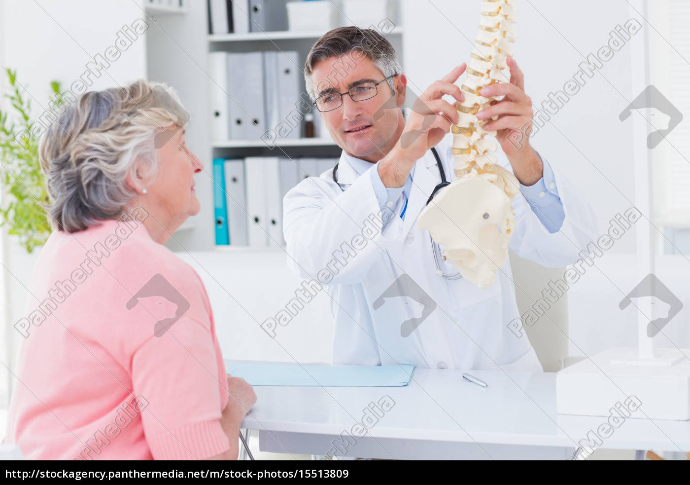 doctor, explaning, anatomical, spine, to, female - 15513809
