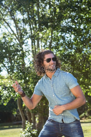 young man playing air guitar in