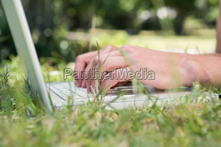 man using laptop in the park