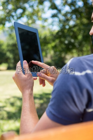 young man using tablet on park