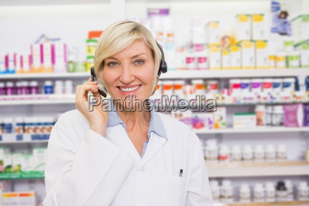 pharmacist with headphone smiling at camera