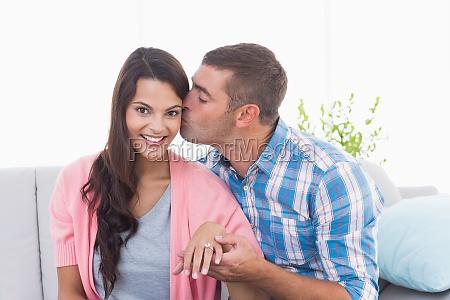 man kissing woman wearing engagement ring
