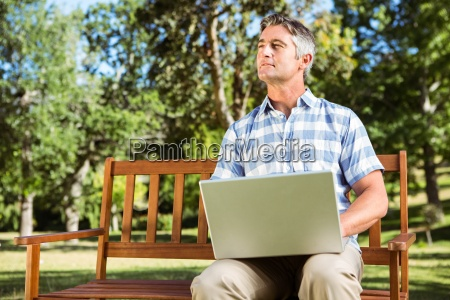 man sitting on park bench using