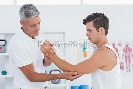 doctor examining his patient arm