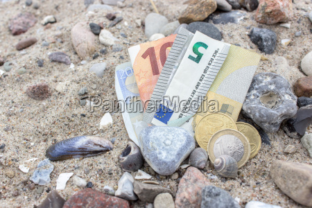 coins bills stones and shells in