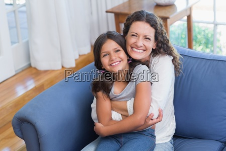 happy mother and daughter sitting on