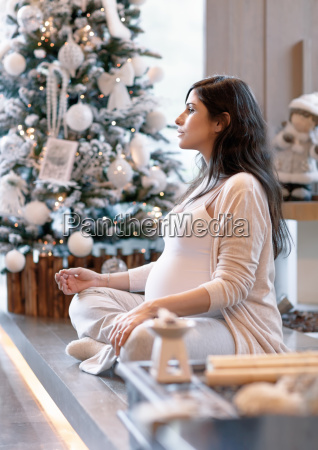 pregnant woman near christmas tree