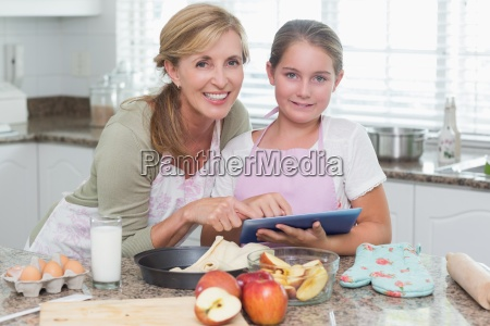 happy mother and daughter preparing cake