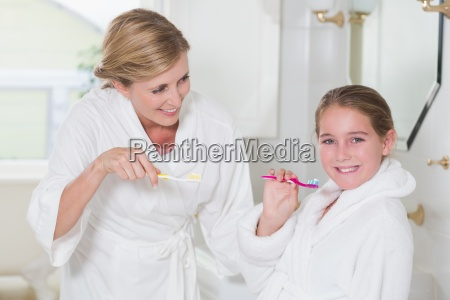 happy mother and daughter brushing teeth