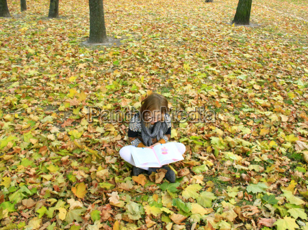 young girl reads a book in