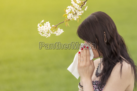 beautiful hayfever girl wiping her nose