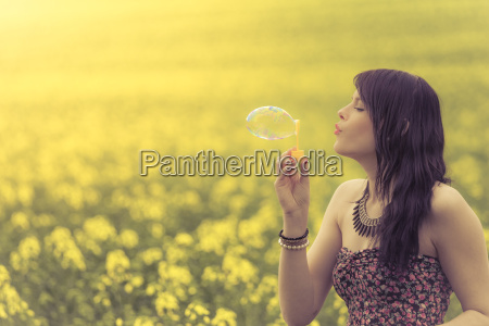 beautiful woman blowing one soap bubble
