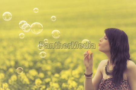beautiful woman blowing many soap bubbles