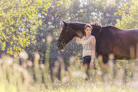 beautiful young equestrian woman with horse