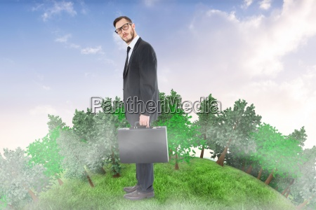 composite image of geeky businessman holding