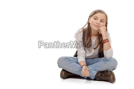young teenager sitting cross legged on