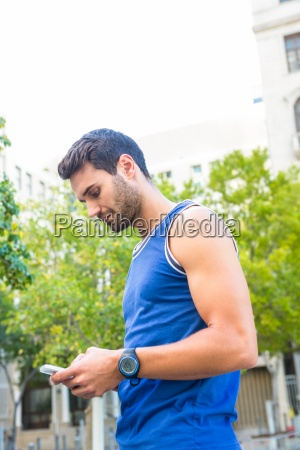 handsome athlete using smartphone