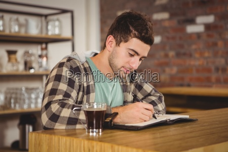 hipster having coffee and writing in