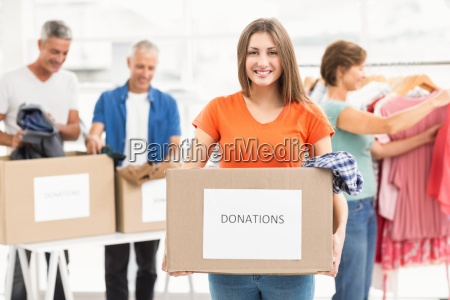 smiling casual businesswoman holding donation box