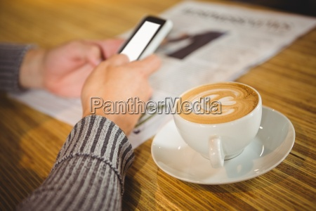 man using smartphone and drinking cappuccino