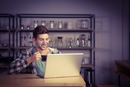 smiling hipster drinking coffee and using