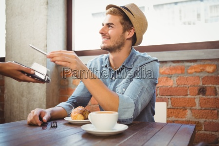 handsome hipster paying with smartphone