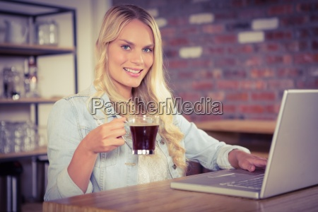 smiling blonde drinking coffee and using