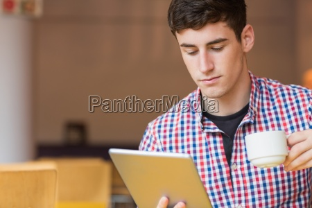 young man using digital tablet while