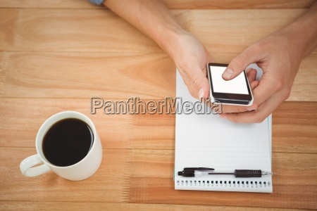 hipster using smartphone with coffee and