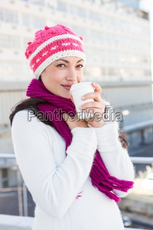smiling woman drinking from white cup