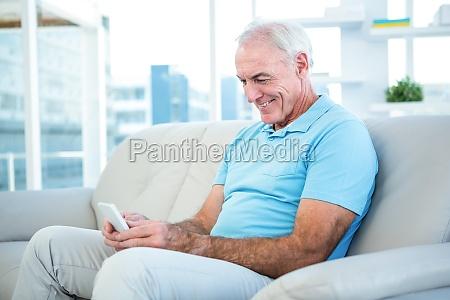 happy senior man using smartphone while
