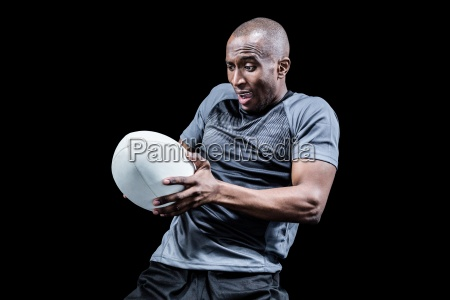 sportsman catching rugby ball while playing