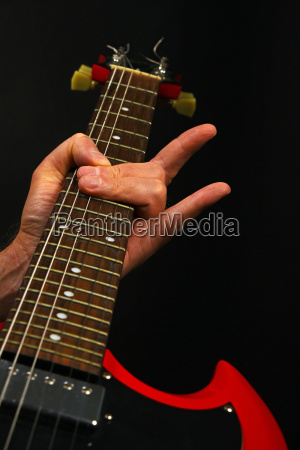 hand with red guitar and devil