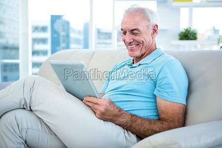 senior man sitting on sofa while