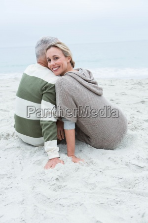 cute couple sitting in the sand