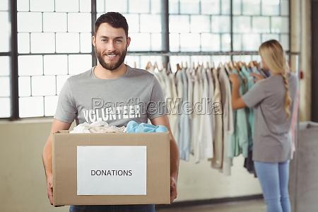 portrait of man holding clothes donation