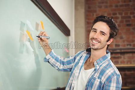 portrait of smiling businessman holding marker