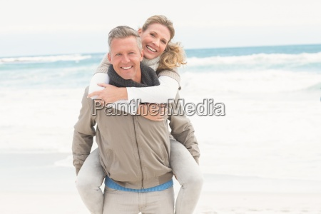smiling man giving woman a piggy