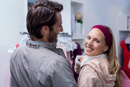 smiling, man, having, arm, around, girlfriend - 15703040
