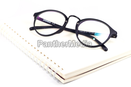 blank spiral notebook and eyeglasses isolated