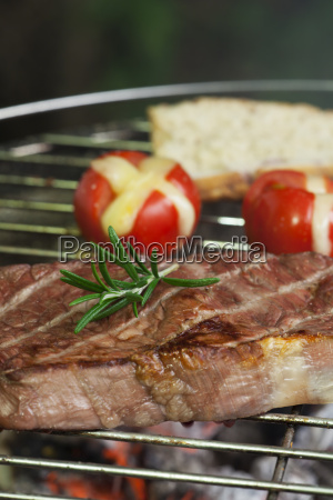 steak on the grill with tomatoes
