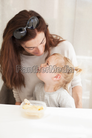 baby eating and looking mother