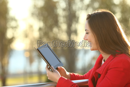 woman reading ebook at sunset