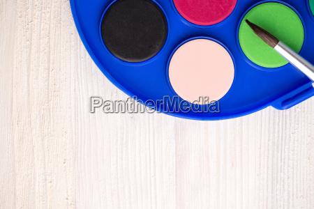paintbrush and paint on wood background